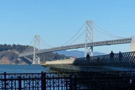 The bridge seen from the Embarcadero promenade. People strolling a pier—this one looks like a footbridge to the island.