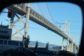 The bridge seen in my side-view mirror as I wait at a traffic light on my way out of the city (San Francisco, California).